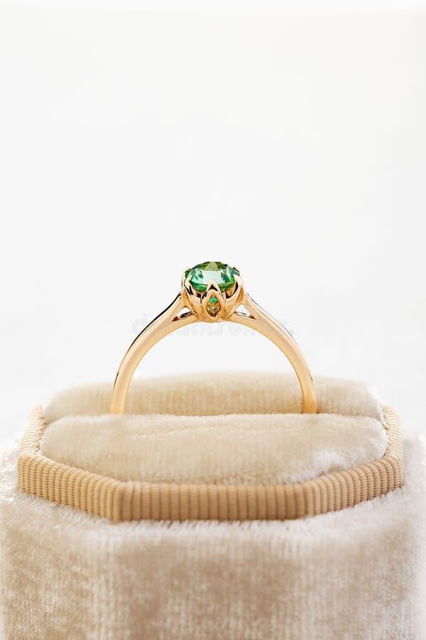 Obrączka ślubna z szmaragdowej zieleni gemstone w beżowym aksamitnym biżuterii pudełku zdjęcie royalty free