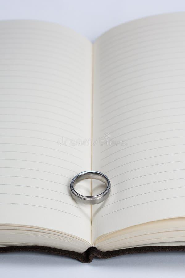 Obrączka Ślubna zespół na książce z Kierowym cienia zakończeniem W górę Odległego Rywalizuje fotografia royalty free