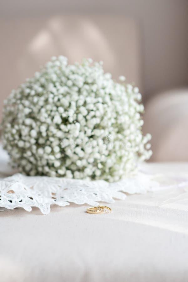 Obrączki ślubne i bridal bukiet nad białą koronkową ślubną suknią - selekcyjna ostrość, kopii przestrzeń, pionowo orientacja zdjęcie stock