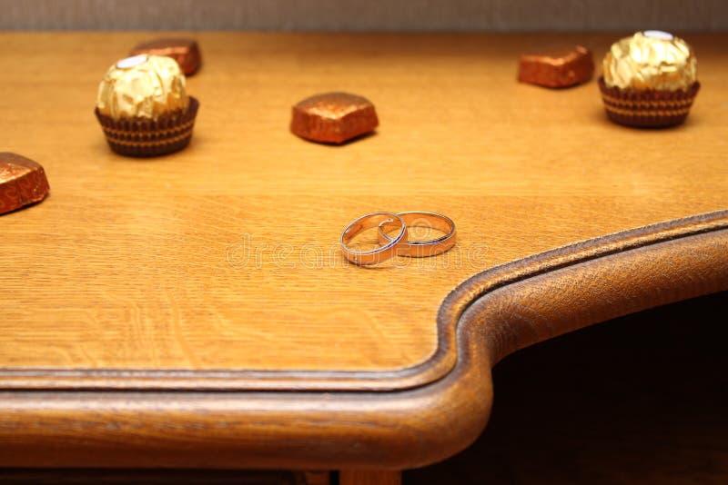 Obrączki ślubne i cukierki na stole zdjęcie royalty free