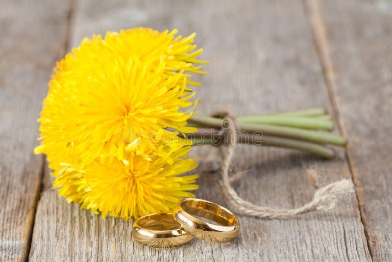 Obrączki ślubne i wiązka żółci dandelion kwiaty obrazy royalty free
