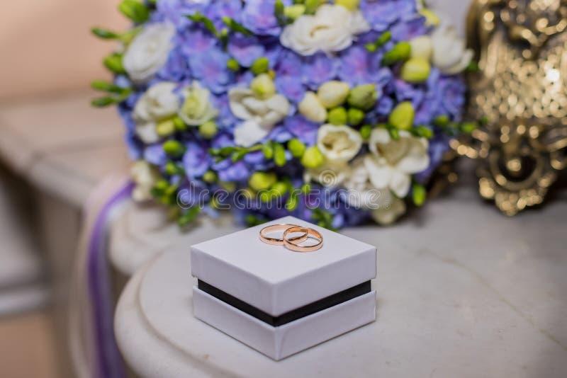 Obrączki ślubne kłamają na białym pudełku na pięknym bukieta tle, jako bridal akcesoria solenny wydarzenie, świąteczny wydarzenie obraz royalty free