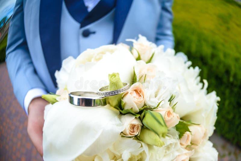 Obrączki ślubne kłamają na pięknym bukiecie jako bridal akcesoria zdjęcia royalty free