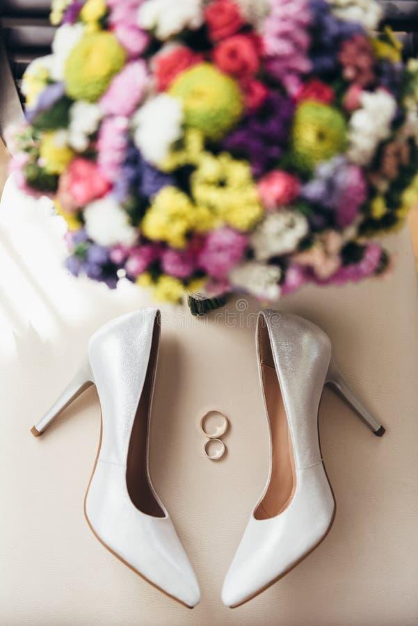 Obrączki ślubne obok bride& x27; s buty i ślubu bukiet obrazy stock