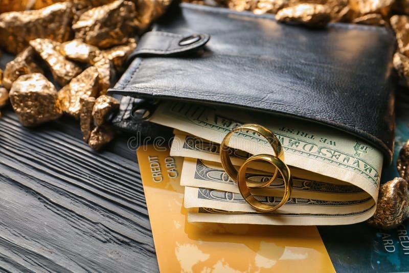 Obrączki ślubne, portfel z pieniądze, karty kredytowe i złoto na stole, Ma??e?stwo dogodno?? zdjęcia royalty free