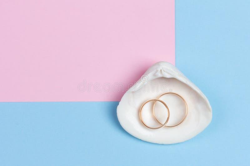 Obr?czki ?lubne w bia?ym seashell na pastelowym b??kit menchii tle fotografia royalty free