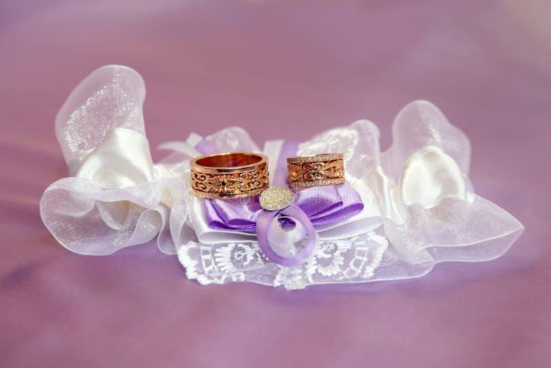 Obrączki ślubnej kłamstwo na pięknie upiększać tkaninach fotografia royalty free
