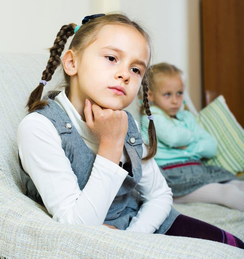 Obrażać dziewczyny siedzi oddzielnie w domu obrazy stock