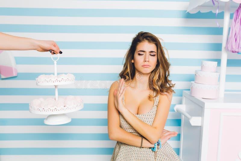 Obrażająca kędzierzawa kobieta w pięknej sukni odmawia jeść marschmellow, stoi na pasiastym tle Portret nieszczęśliwy zdjęcie royalty free