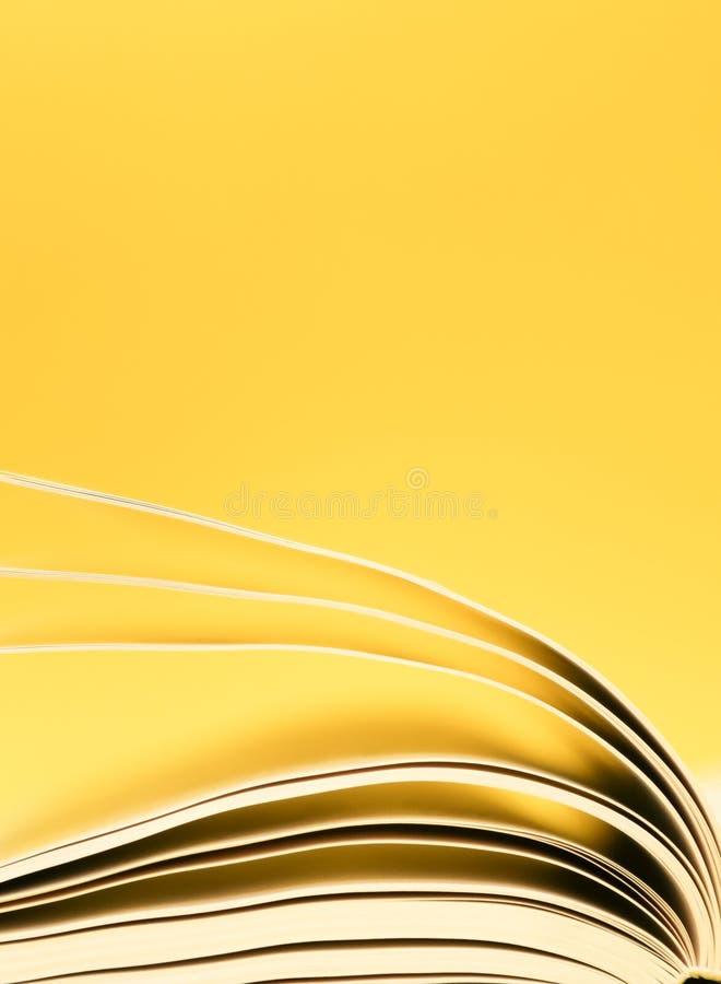 Obracanie stron księgi, przewracanie stron na żółte tło obrazy royalty free