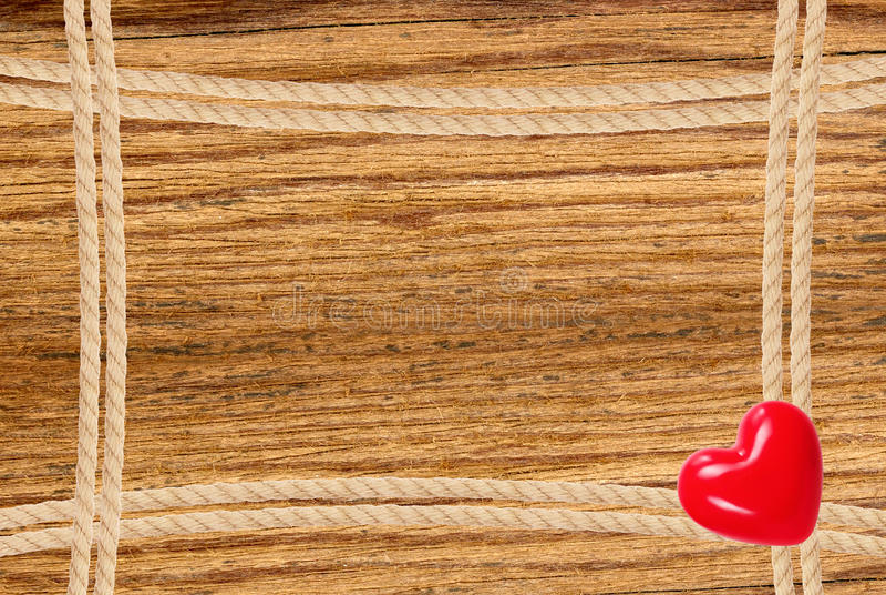 Obramia opanowanego linowy i czerwony serce nad drewnianym tłem fotografia royalty free