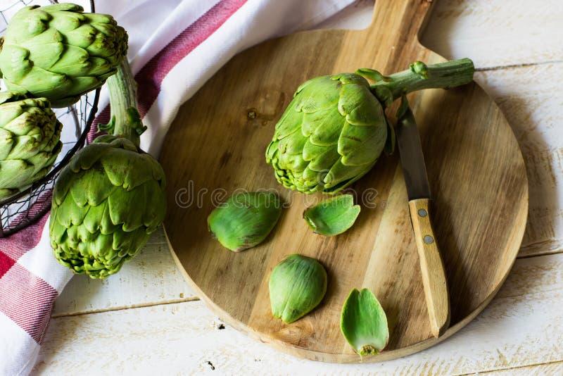 Obrany świeży karczocha narządzanie dla gotować, drewniana tnąca deska, nóż, warzywa w metalu koszu, nieociosany kuchenny wnętrze fotografia stock