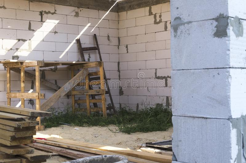 Obras home Escada e andaime de madeira perto da parede de tijolo fotos de stock