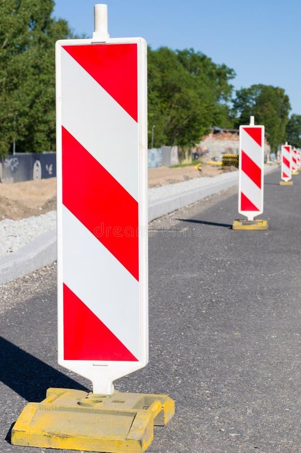 Obras viales marcadas con los posts amonestadores del camino rayado fotos de archivo libres de regalías