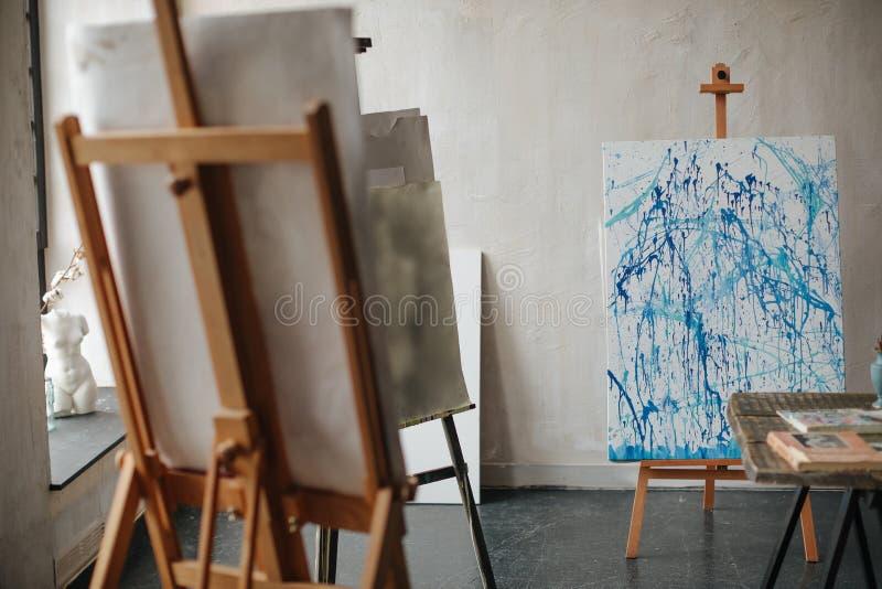 Obrazek artysta z pluśnięciami błękitna farba w warsztacie na sztaludze fotografia royalty free
