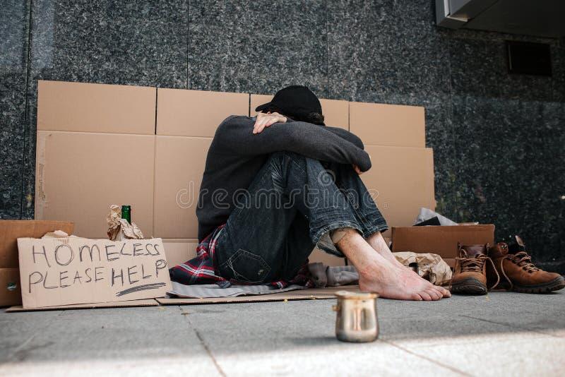 Obrazek beznadziejny mężczyzna obsiadanie na kartonie i chować jego twarz Zakrywa ja z rękami i patrzeć w dół zdjęcia royalty free