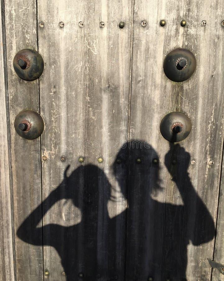 Obrazek cień kobiety i mężczyzna który dzwoni na sfałszowanym doorbell na drewnianym drzwi zdjęcia royalty free