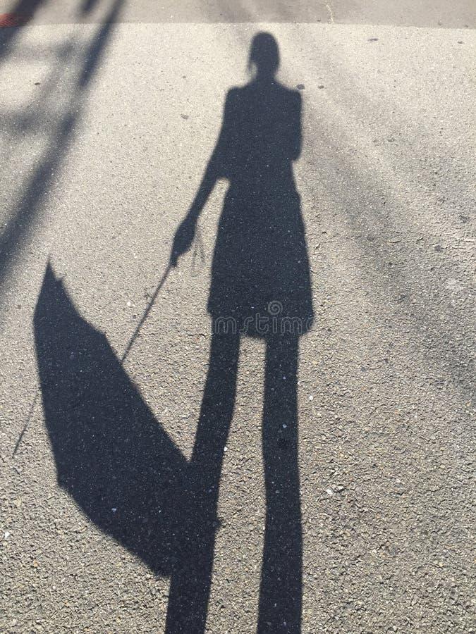 Obrazek cień kobiety trzyma puszek jej parasol zdjęcia stock