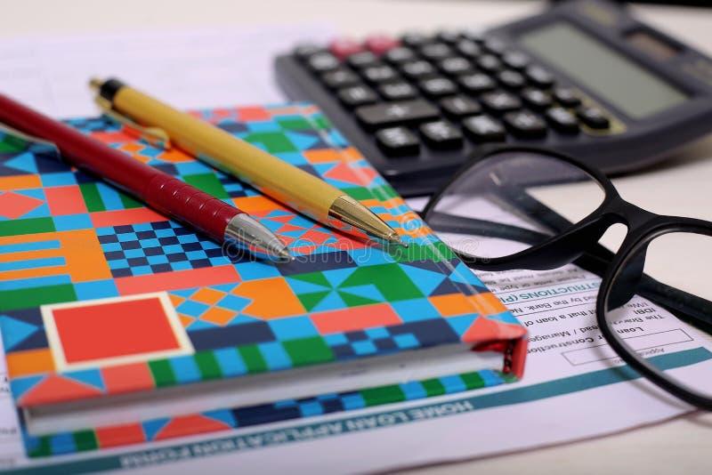 Obrazek kalkulator, dwa pisze, notatnik, forma i szkła, zdjęcia stock