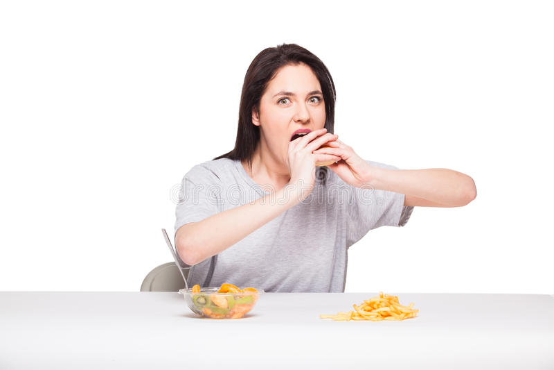 Obrazek kobieta z owoc i hamburgerem w przodzie na białym bac obrazy royalty free