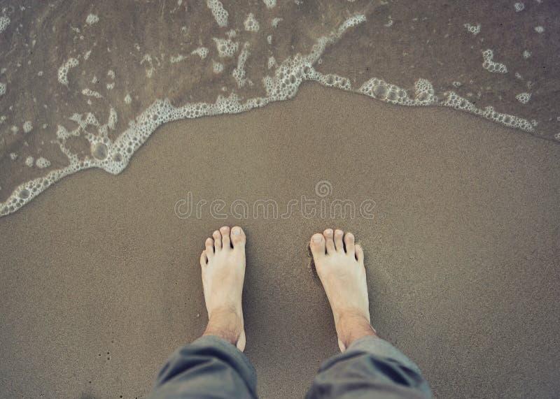 Obrazek męska naga stopa blisko wody morskiej zdjęcie royalty free