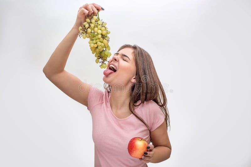 Obrazek młodej kobiety mienia winogrona nad rozpieczętowany usta Dosięga mnie z jęzorem Apple w innej ręce Odizolowywający dalej fotografia stock