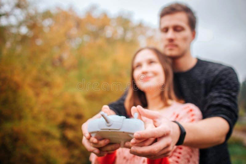 Obrazek młody człowiek i kobieta stoi wpólnie i trzyma pilota do tv od trutnia Jest za ona spojrzenia up kobiety zdjęcie royalty free