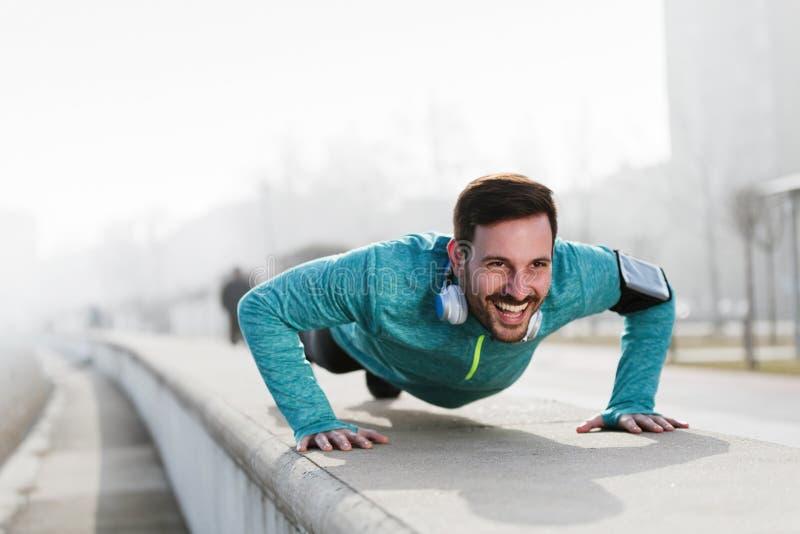 Obrazek młody sportowiec podnosi outdoors robić pcha fotografia stock