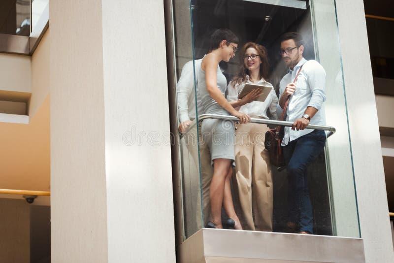 Obrazek młodzi biznesmeni opowiada w windzie obraz stock