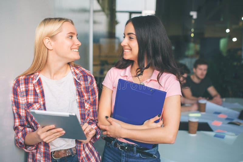 Obrazek młodzi blondynki i brunetki modele stoi wpólnie i ono uśmiecha się Patrzeją szczęśliwymi Młode kobiety trzymają elektroni obraz royalty free