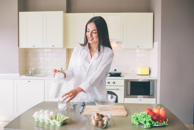 Obrazek piękna dziewczyny pozycja w kuchni i dolewania mleku w szklanej filiżance Jest przyglądająca ja i ono uśmiecha się Dziewc fotografia royalty free