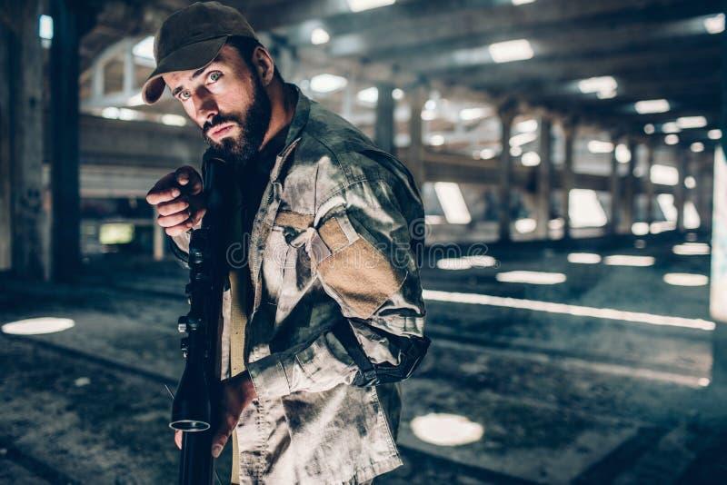 Obrazek pozuje na kamerze wojskowy Jest w dużym hangarze Trzyma czarnego karabin i przygotowywa strzelać Facet jest fotografia royalty free