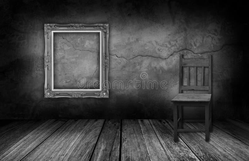 Obrazek rama i drewniany krzesło w wewnętrznym pokoju z szarą kamienną ścianą obraz stock