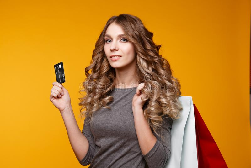 Obrazek rozochocona młoda brunetki kobieta w białej lato sukni mienia karcie kredytowej pozuje z torbami na zakupy i zdjęcie stock