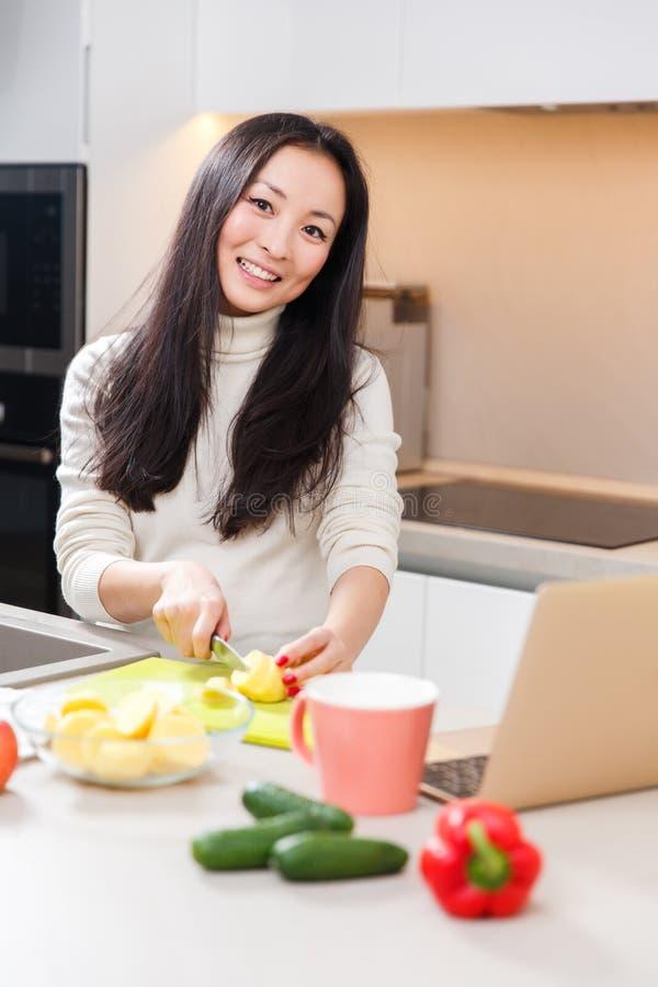 Obrazek szczęśliwa azjatykcia dziewczyna z kubka, laptopu pozycją przy stołem z i obrazy royalty free
