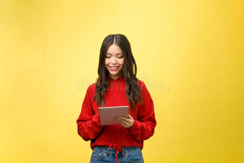 Obrazek szczęśliwa nastoletnia dziewczyna z pastylka komputeru osobistego komputerem odizolowywa na żółtym tle zdjęcie stock