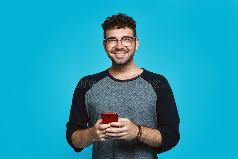 Obrazek uśmiechnięty brodaty mężczyzna pisze wiadomości na smartphone nad błękitnym tłem z eyeglasses fotografia royalty free
