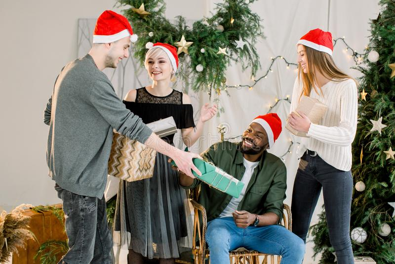 Obrazuje pokazywać grupy przyjaciele świętuje boże narodzenia w domu i wymienia boże narodzenie prezenty zdjęcia stock