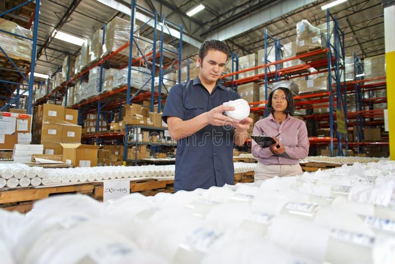 Obrero y encargado que controlan mercancías en cadena de producción imagenes de archivo