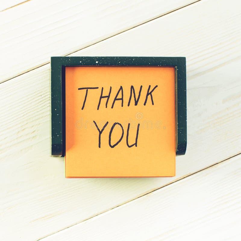 Obrigado escrito na etiqueta da nota do cargo na tabela de madeira clara, a foto de stock