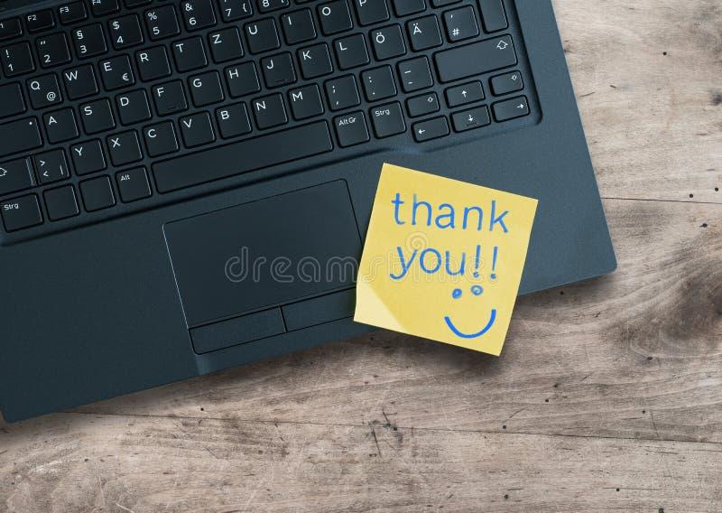 Obrigado escrito na nota pegajosa no laptop imagens de stock royalty free
