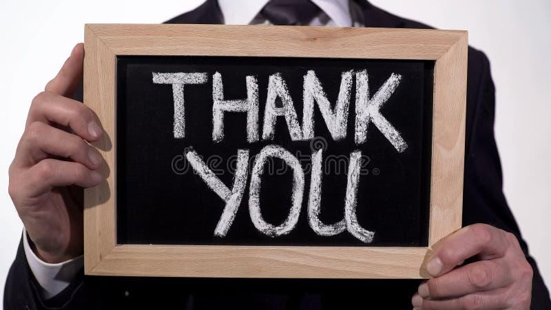Obrigado escrito no quadro-negro nas mãos do homem de negócios, apreciação da doação fotos de stock