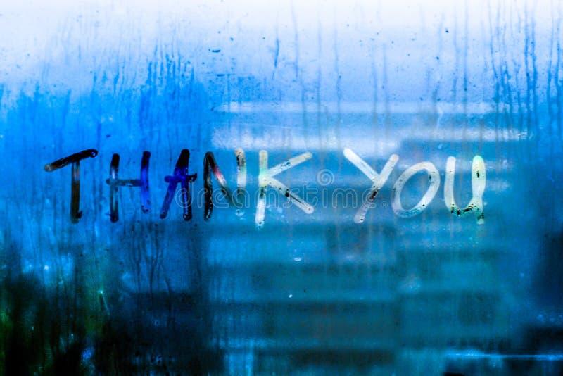 Obrigado exprime gotas que da chuva a água deixa cair o wrie escrito no fundo azul do bokeh da natureza do borrão do tom do vidro fotografia de stock royalty free