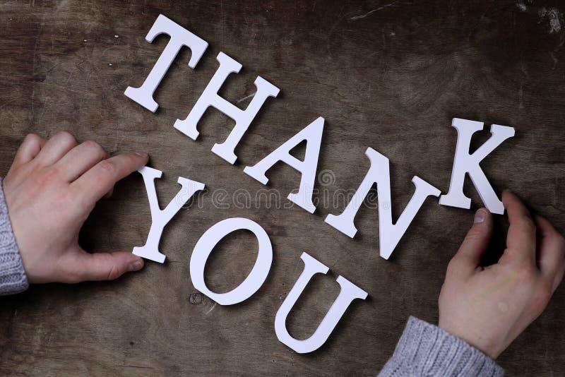 Obrigado exprimir das letras de madeira brancas na tabela e nas mãos fotografia de stock royalty free