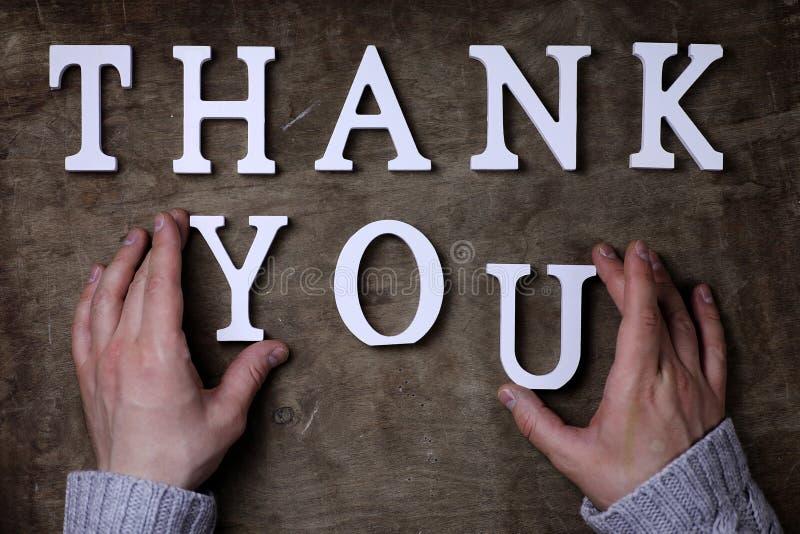 Obrigado exprimir das letras de madeira brancas na tabela e nas mãos imagem de stock royalty free