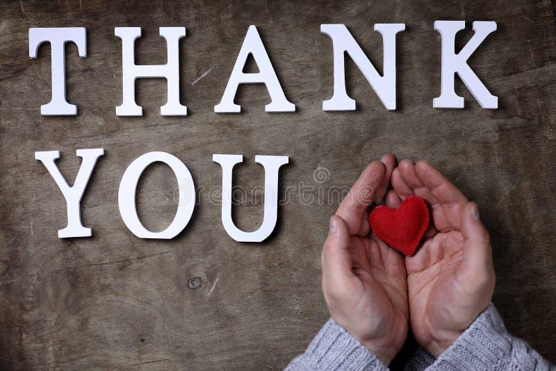 Obrigado exprimir das letras de madeira brancas na tabela e nas mãos imagem de stock