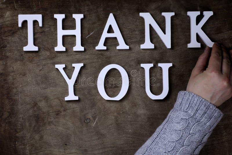 Obrigado exprimir das letras de madeira brancas na tabela e nas mãos fotos de stock royalty free