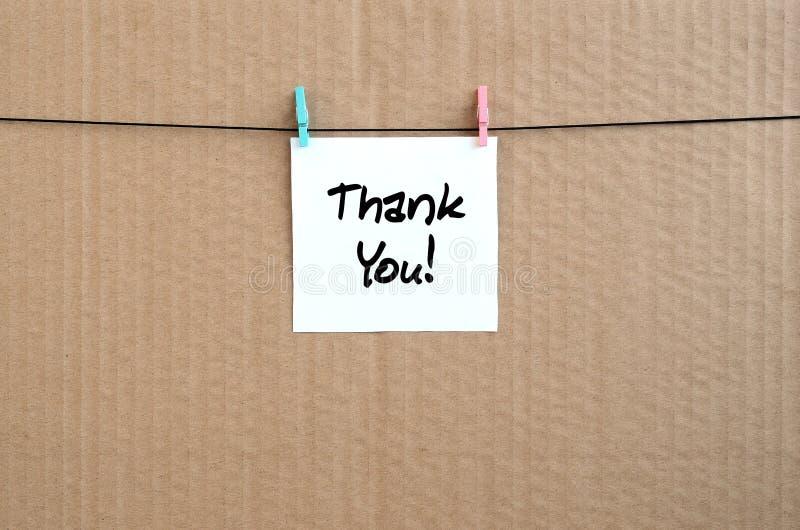 Obrigado! A nota é escrita em uma etiqueta branca que pendure com a imagens de stock