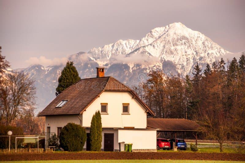 Obrzeża Zagreb: Tradycyjny Wiejski dom z śnieg Nakrywającym Halnym tłem zdjęcia royalty free