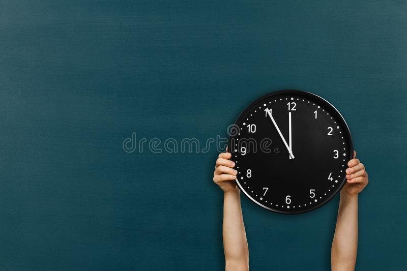Obsługuje chwyta round ściennego zegar na chalkboard tle fotografia stock